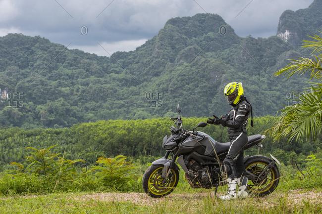 Woman preparing to ride motorbike around Khao Sok National Park, Thailand