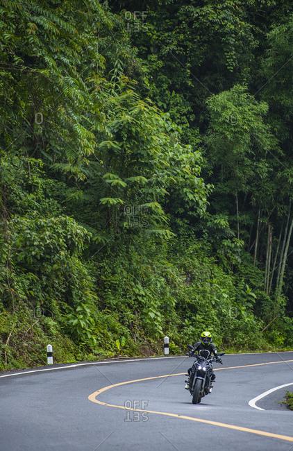 Woman riding motorbike around Khao Sok National Park, Thailand