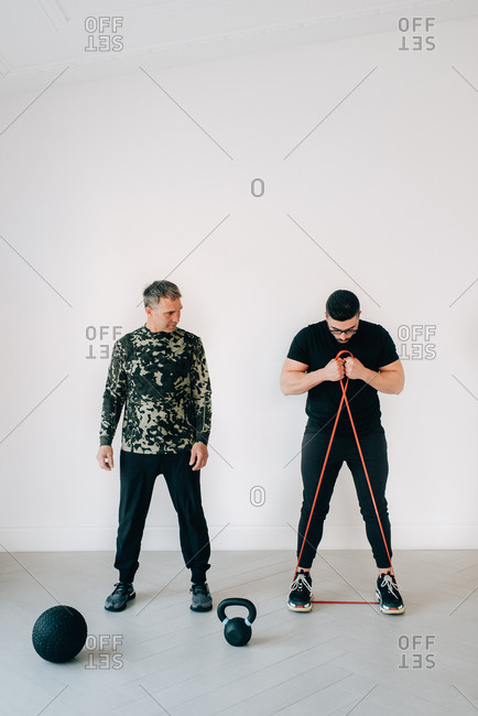 Fitness instructor teaching man using resistance band in studio