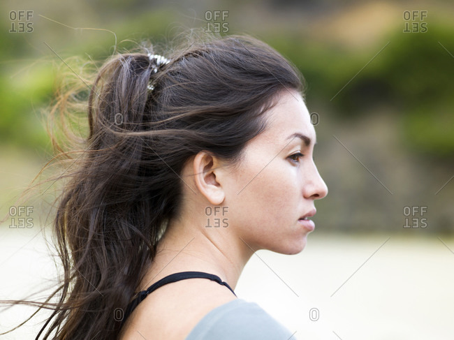 Young female surfer gazing from beach, head and shoulder side view, Victoria, Australia