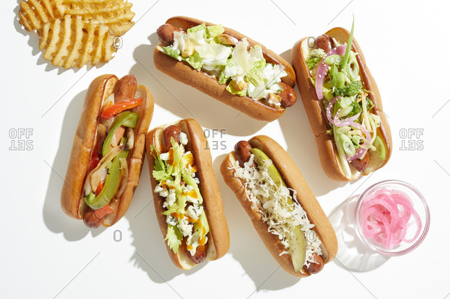 Selection of hotdogs with varied garnish and waffle fries, overhead view