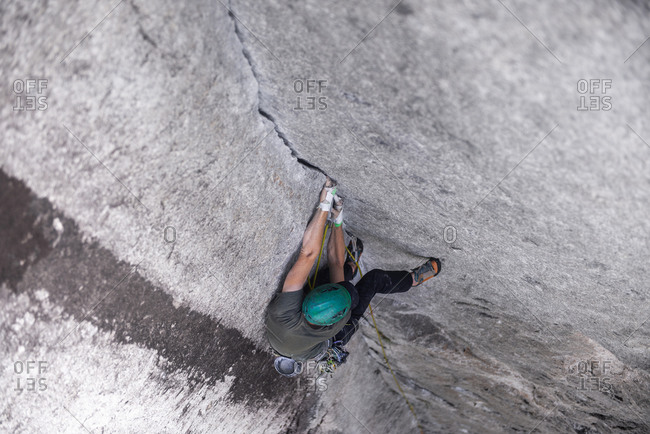 Rock climber on The Daily Planet route on The Chief in Squamish, Canada