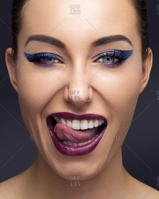 Beautiful young woman with full make up sticking out tongue