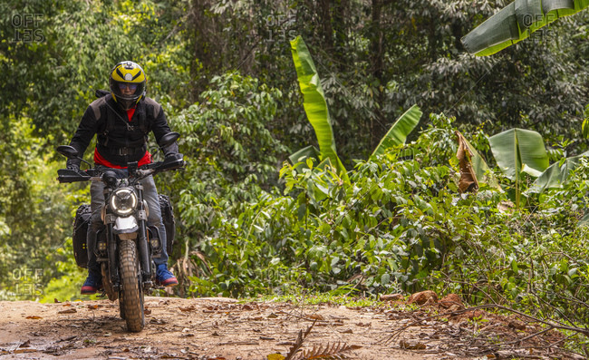 Biker riding off road motorcycle on dirt road through forest, Chiang Mai, North Thailand