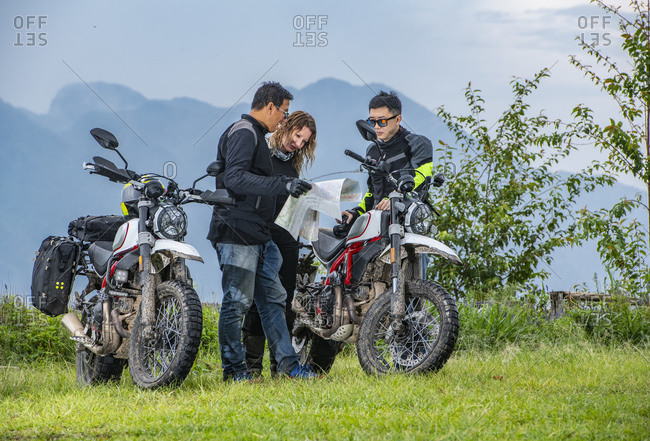 Bikers checking map next to off road motorcycles, mountains in background, Chiang Mai, North Thailand
