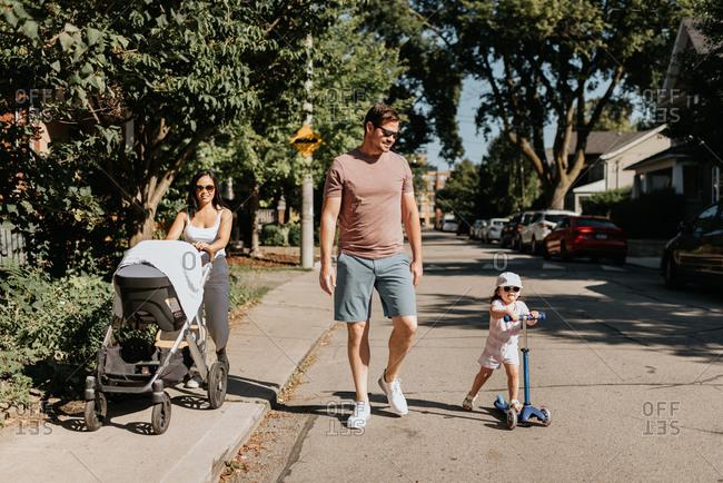 Family of four taking walk in neighborhood