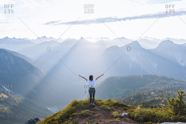 Female hiker raising arms against sun on peak, Winchester Mountain, North Cascades, Washington, USA