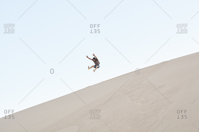 Hiker jumping in mid air on sand dunes, Great Sand Dunes National Park and Preserve, Colorado, USA