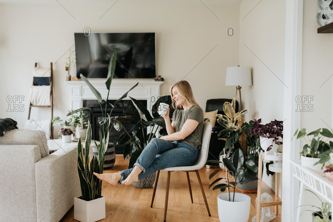 Woman relaxing with warm beverage in room full of house plants