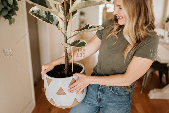 Woman carrying large pot of house plant