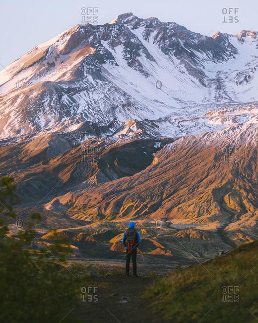 Hiker admiring Mount St Helens National Monument from afar, Washington, USA