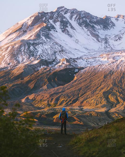 Hiker admiring Mount St Helens National Monument from afar, Washington, USA