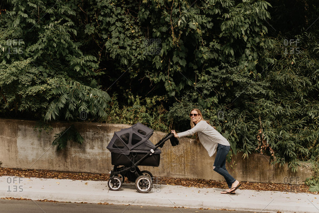 Mother pushing baby carriage up pavement
