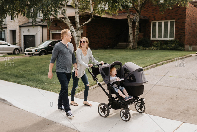 Couple taking toddler in baby carriage for walk in neighborhood