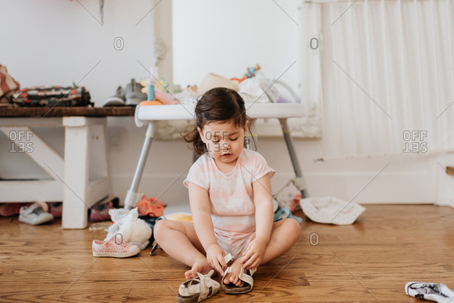 Toddler putting on shoes in living room