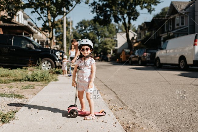 Toddler riding on push scooter in neighborhood, family in background
