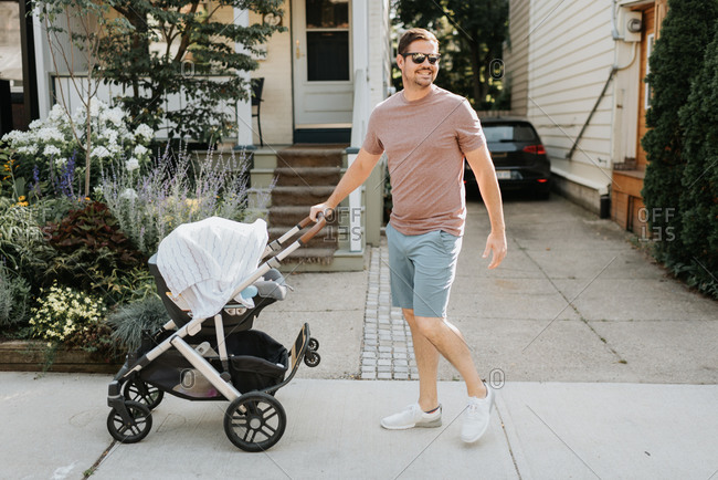 Father pushing baby carriage on pavement