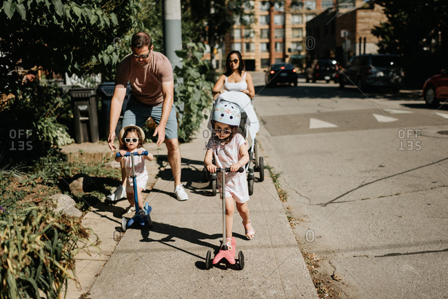 Couple and daughters playing push scooter in neighborhood