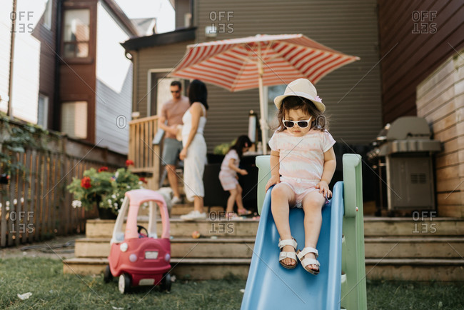 Toddler playing on slide, family members in background