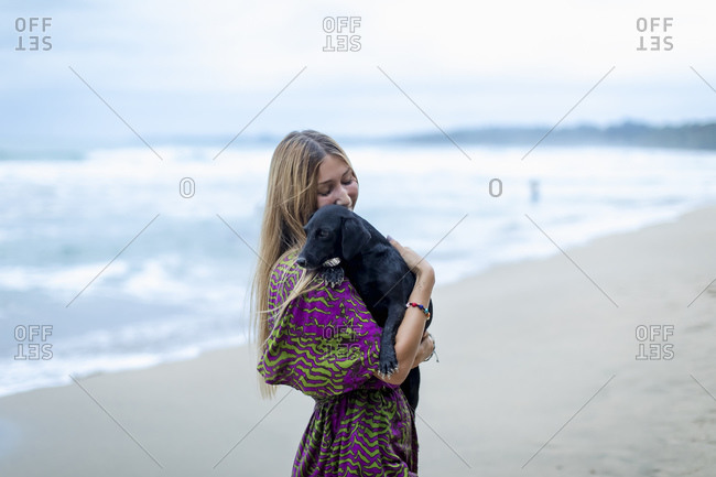 Woman hugging pet dog on beach after sunset, Cahuita, Costa Rica