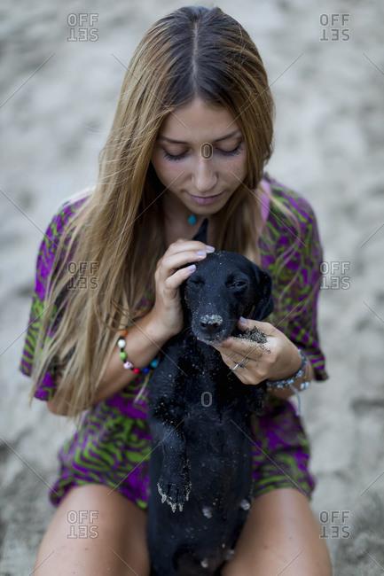 Woman hugging pet dog on beach after sunset, Cahuita, Costa Rica