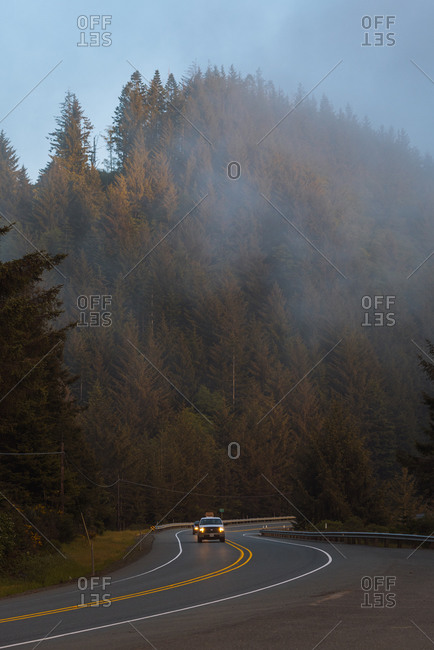Vehicles driving down windy road on foggy afternoon along coast, Redwood forest, California, USA