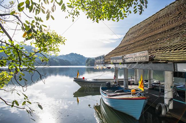 September 26, 2019: Boats moored at boat house, Kandy Lake (Kiri Muhuda or Sea of Milk), artificial lake in heart of hill city, Kandy, Sri Lanka