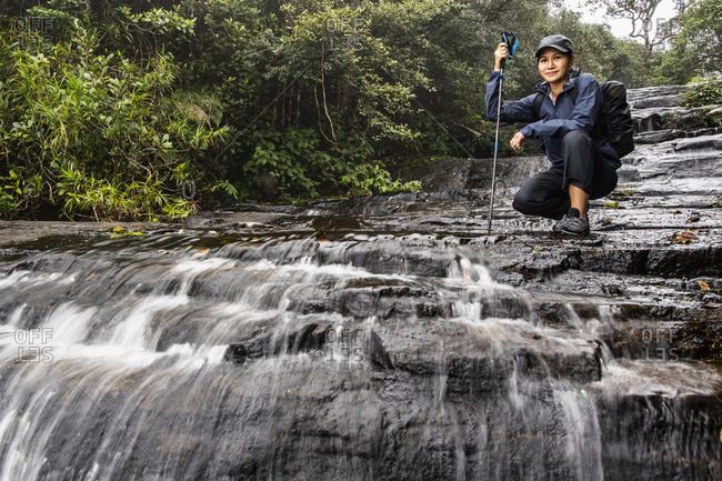Female hiker posing in waterfall, Madulkelle, Sri Lanka