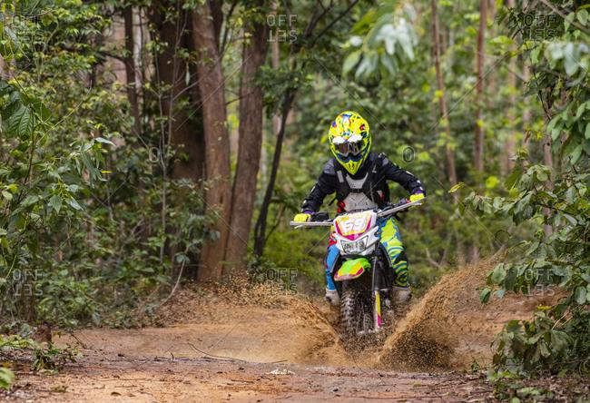 Biker riding off road motorbike through muddy water, Nakhon Ratchasima, Thailand