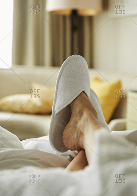 Person's foot with bedroom slipper resting on bed in hotel room