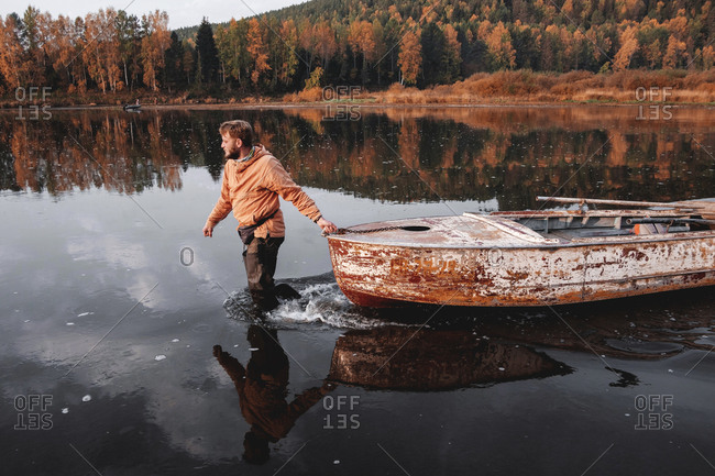 Man dragging old rusty boat in middle of lake in autumn, Russia