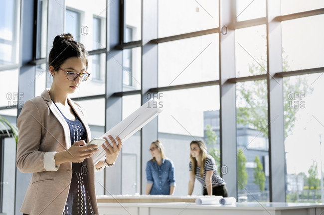 Portrait of young businesswoman with dark brown hair wearing glasses standing in office, reading.