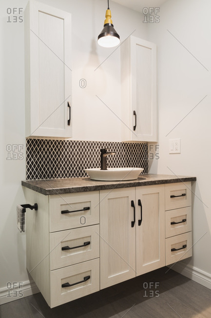 Antique finish wooden cabinet with black nuanced laminated countertop and ceramic backsplash in bathroom inside contemporary home, Quebec, Canada.