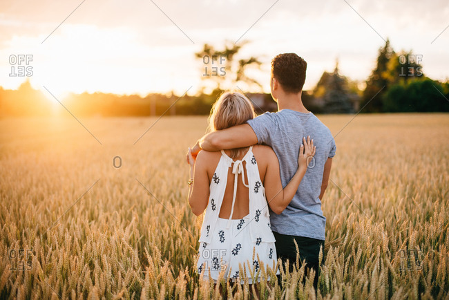 Smiling young couple standing in golden wheat field, smiling at each other.
