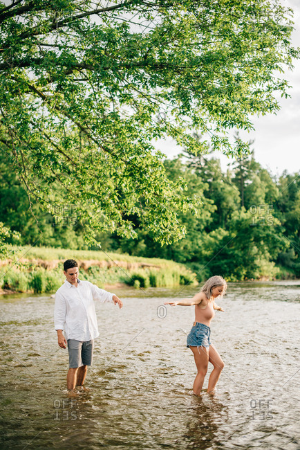Young couple standing ankle deep in a river, using their mobile phones to take pictures.