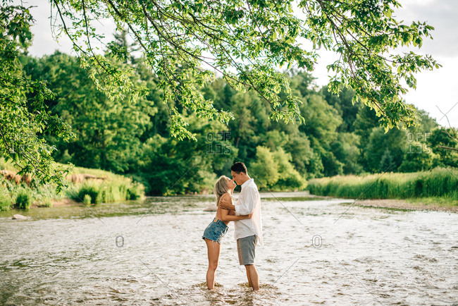 Young couple sitting on a riverbank, smiling at each other and hugging.