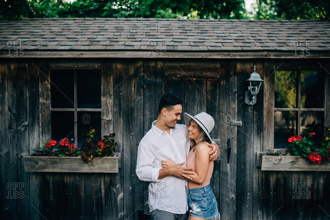 Young couple standing outside wooden hut, hugging and smiling at each other.