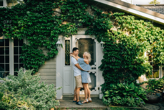 Young couple standing outside cottage, hugging and smiling at each other.