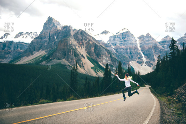 Woman jumping in mid air on road, Jasper, Canada
