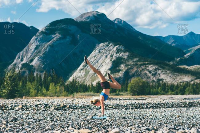 Woman doing handstand on field of stones, Jasper, Canada