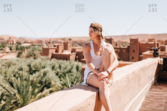 Woman enjoying view on stonewall, Ouarzazate, Souss-Massa-Draa, Morocco