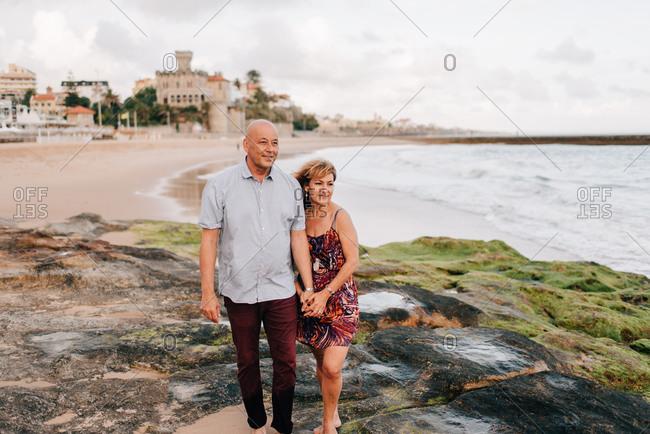Couple taking walk on beach, Estoril, Lisboa, Portugal