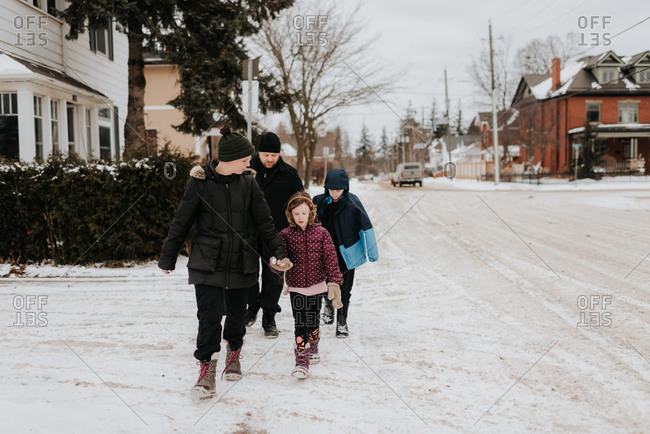 Parents and children walking on snow covered street