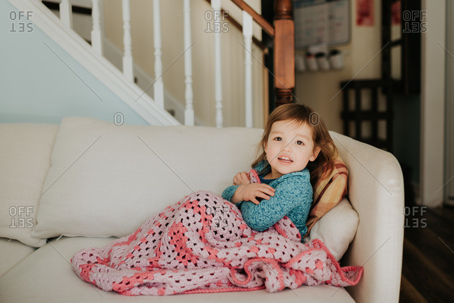 Female toddler on sofa with blanket, portrait