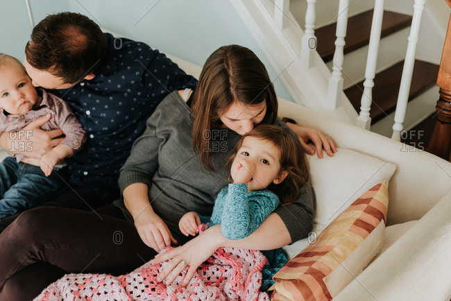 Mid adult couple on sofa with baby son and toddler daughter