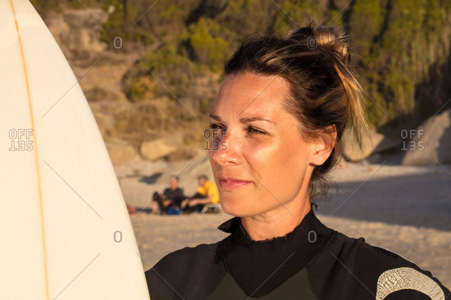 Female surfer carrying surfboard on beach, head and shoulder, Cape Town, Western Cape, South Africa