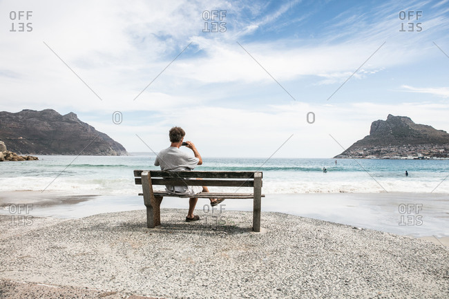 Mature man taking photograph from beach bench, Cape Town, Western Cape, South Africa