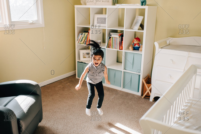 Girl jumping mid air in nursery, portrait