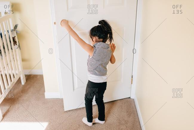 Girl opening nursery door, rear view
