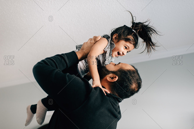 Girl being held up by father, side view